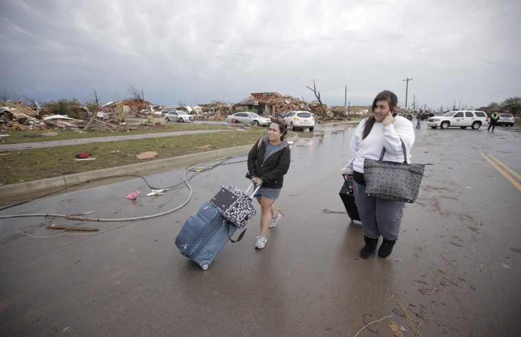 Ashley Do (Left) and Bonnie Lolofie walk from their apartment that has no power or water but was otherwise undamaged by yesterday's tornado on May 21, 2013 in Moore, Oklahoma. The town reported a tornado of at least EF4 strength and two miles wide that touched down yesterday killing at least 24 people and leveling everything in its path. U.S. President Barack Obama promised federal aid to supplement state and local recovery efforts. (Brett Deering/Getty Images)