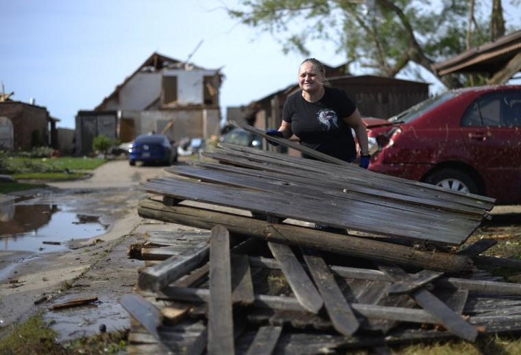 Alyssa McDowell cleans debris from her tornado devastated houses on May 21, 2013 in Moore, Oklahoma. Families returned to a blasted moonscape that had been an American suburb Tuesday after a monstrous tornado tore through the outskirts of Oklahoma City, killing at least 24 people. Nine children were among the dead and entire neighborhoods vanished, with often the foundations being the only thing left of what used to be houses and cars tossed like toys and heaped in big piles. (Jewel Samad/AFP/Getty Images)