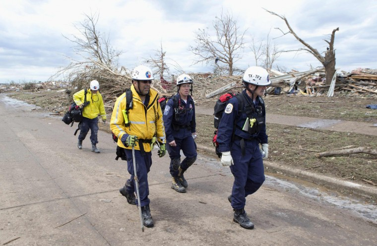 Recovery workers walk through the destruction in a neighborhood in Moore, Oklahoma May 21, 2013. Rescuers went building to building in search of victims and thousands of survivors were homeless on Tuesday, a day after a massive tornado tore through a suburb of Oklahoma City, wiping out whole blocks of homes and killing at least 24 people. (Richard Rowe/Reuters photo)