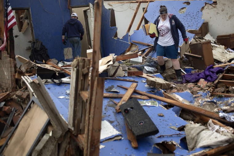 Residents salvage their belongings after their house was left devastated by a tornado in Moore, Oklahoma, in the outskirts of Oklahoma City on May 21, 2013. Rescuers went building to building in search of victims and thousands of survivors were homeless on Tuesday, a day after a massive tornado tore through a suburb of Oklahoma City, wiping out whole blocks of homes and killing at least 24 people. (Adrees Latif/Reuters photo)