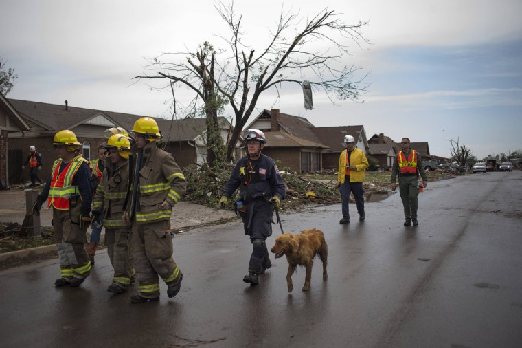Rescue workers use a canine while searching house-to-house for survivors in a neighborhood left devastated by a tornado in Moore, Oklahoma, in the outskirts of Oklahoma City May 21, 2013. Rescuers went building to building in search of victims and thousands of survivors were homeless on Tuesday, a day after a massive tornado tore through a suburb of Oklahoma City, wiping out whole blocks of homes and killing at least 24 people. Emergency workers pulled more than 100 survivors from the rubble of homes, schools and a hospital, and around 237 people were injured. Cadaver dogs sniffed through the scattered planks and bricks of ruined homes on Tuesday. (Adrees Latif/Reuters photo)