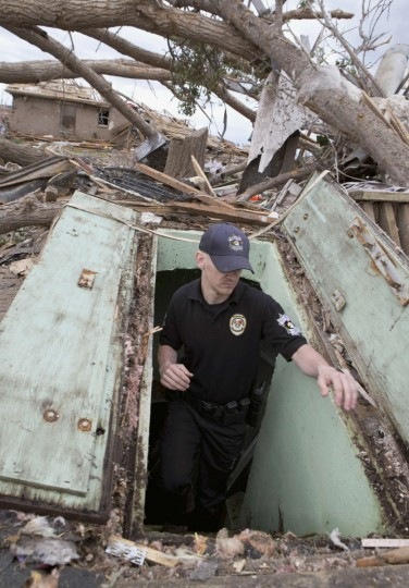 Oklahoma County Sheriff's Deputy Erik Gransberg searches for victims in an underground shelter in Moore, Oklahoma May 21, 2013. Rescuers went building to building in search of victims and thousands of survivors were homeless on Tuesday, a day after a massive tornado tore through a suburb of Oklahoma City, wiping out whole blocks of homes and killing at least 24 people. (Richard Rowe/Reuters photo)