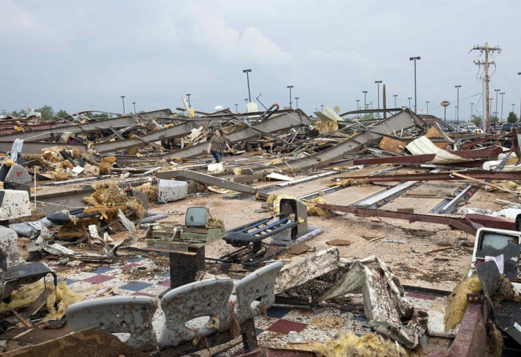 A woman walks through debris after a huge tornado struck Moore, Oklahoma, near Oklahoma City, May 20, 2013. A massive tornado tore through the Oklahoma City suburb of Moore on Monday, killing at least 51 people as winds of up to 200 miles per hour (320 kph) flattened entire tracts of homes, two schools and a hospital, leaving a wake of tangled wreckage. (Richard Rowe/Reuters photo)