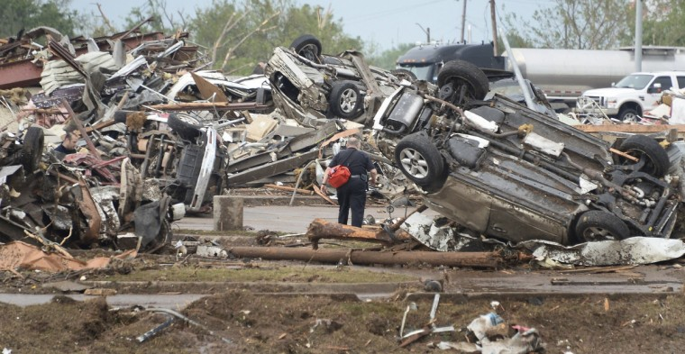 A rescue worker looks for victims in the Moore Hospital parking lot after being hit by a tornado that destroyed buildings and overturned cars in Moore, Oklahoma, near Oklahoma City, May 20, 2013. A huge tornado with winds of up to 200 miles per hour (320 kph) devastated the Oklahoma City suburb of Moore on Monday, ripping up at least two elementary schools and a hospital and leaving a wake of tangled wreckage. At least four people were killed, KFOR television said, citing a reporter's eyewitness account, and hospitals said dozens of people were injured. (Gene Blevins/Reuters photo)