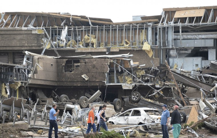 People survey the destructions at the Moore hospital after it was hit by a tornado that destroyed buildings and overturned cars in Moore, Oklahoma, May 20, 2013. A huge tornado with winds of up to 200 miles per hour (320 kph) devastated the Oklahoma City suburb of Moore on Monday, ripping up at least two elementary schools and a hospital and leaving a wake of tangled wreckage. (Gene Blevins/Reuters photo)