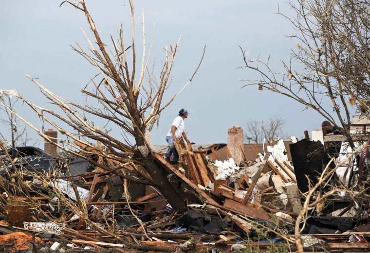 A man looks through the remains of a home after a huge tornado struck Moore, Oklahoma, near Oklahoma City, May 20, 2013. A massive tornado tore through the Oklahoma City suburb of Moore on Monday, killing at least 51 people as winds of up to 200 miles per hour (320 kph) flattened entire tracts of homes, two schools and a hospital, leaving a wake of tangled wreckage. (Richard Rowe/Reuters photo)