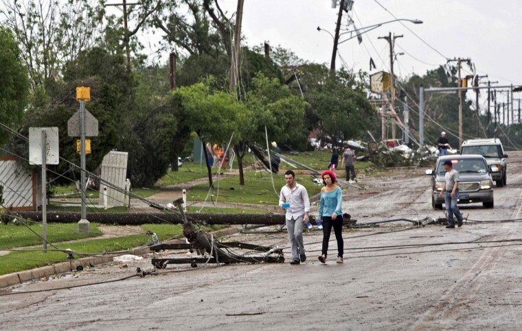 Downed power lines block a road after a huge tornado struck Moore, Oklahoma, near Oklahoma City, May 20, 2013. A massive tornado tore through the Oklahoma City suburb of Moore on Monday, killing at least 51 people as winds of up to 200 miles per hour (320 kph) flattened entire tracts of homes, two schools and a hospital, leaving a wake of tangled wreckage. (Richard Rowe/Reuters photo)