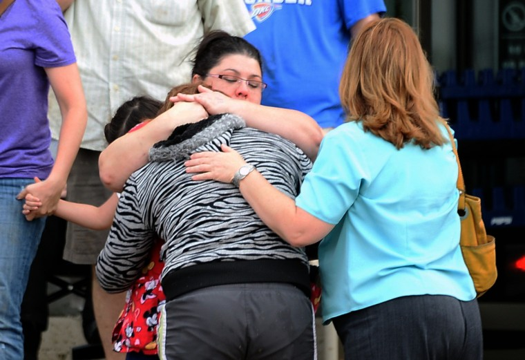 A woman is comforted after a tornado that destroyed buildings and overturned cars struck Moore, Oklahoma, May 20, 2013. A huge tornado with winds of up to 200 miles per hour (320 kph) devastated the Oklahoma City suburb of Moore on Monday, ripping up at least two elementary schools and a hospital and leaving a wake of tangled wreckage. (Gene Blevins/Reuters photo)
