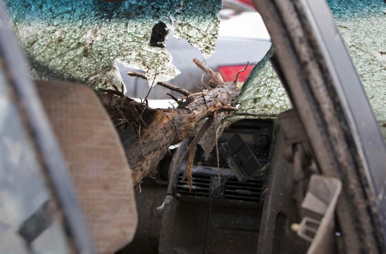 A tree branch lies on top of a broken windshield after a huge tornado struck Moore, Oklahoma, near Oklahoma City, May 20, 2013. A massive tornado tore through the Oklahoma City suburb of Moore on Monday, killing at least 51 people as winds of up to 200 miles per hour (320 kph) flattened entire tracts of homes, two schools and a hospital, leaving a wake of tangled wreckage. (Richard Rowe/Reuters photo)