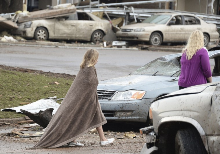 A girl tries to keep warm near the Moore Hospital after being hit tornado that destroyed buildings and overturned cars in Moore, Oklahoma, May 20, 2013. A huge tornado with winds of up to 200 miles per hour (320 kph) devastated the Oklahoma City suburb of Moore on Monday, ripping up at least two elementary schools and a hospital and leaving a wake of tangled wreckage. (Gene Blevins/Reuters photo)