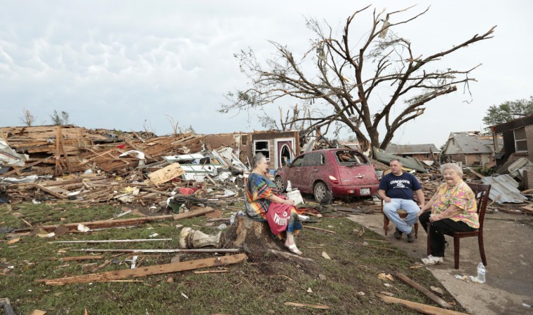 Yvonne Barragar, left, Joe Marshall, center, and Barbara Garcia, right, sit in front of Barragar's destroyed house after a powerful tornado ripped through the area on May 20, 2013 in Moore, Oklahoma. The tornado, reported to be at least EF4 strength and two miles wide, touched down in the Oklahoma City area on Monday killing at least 51 people. (Brett Deering/Getty Images)