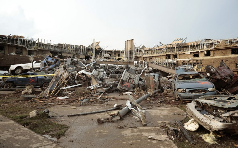 Cars marked with an orange 'X', denoting they had been checked for occupants, are piled up in what was the front entrance to the damaged Moore Medical Center after a powerful tornado ripped through the area on May 20, 2013 in Moore, Oklahoma. The tornado, reported to be at least EF4 strength and two miles wide, touched down in the Oklahoma City area on Monday killing at least 51 people. (Brett Deering/Getty Images)