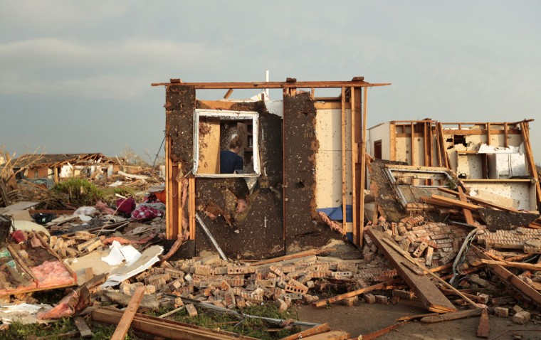 Dana Ulepich searches inside a room left standing at the back of her house destroyed after a powerful tornado ripped through the area on May 20, 2013 in Moore, Oklahoma. The tornado, reported to be at least EF4 strength and two miles wide, touched down in the Oklahoma City area on Monday killing at least 51 people. (Brett Deering/Getty Images)