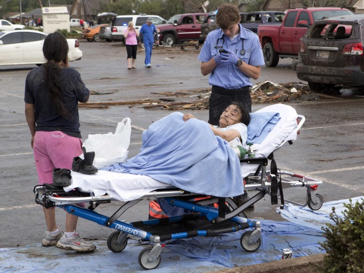 A woman is tended to by a Emergency Medical Technician after a huge tornado struck Moore, Oklahoma, near Oklahoma City, May 20, 2013. A massive tornado tore through the Oklahoma City suburb of Moore on Monday, killing at least 51 people as winds of up to 200 miles per hour (320 kph) flattened entire tracts of homes, two schools and a hospital, leaving a wake of tangled wreckage. (Richard Rowe/Reuters photo)