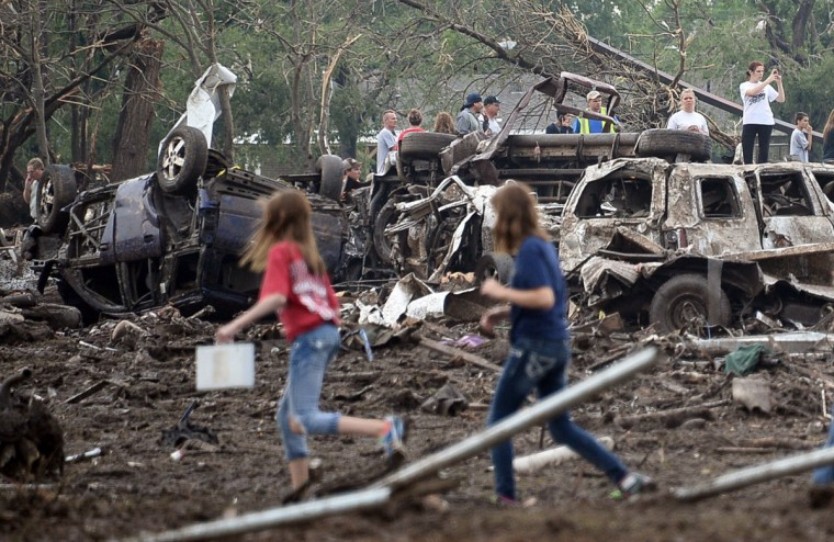 People look through the wreckage of their neighborhood after a tornado struck Moore, Oklahoma, May 20, 2013. A huge tornado with winds of up to 200 miles per hour (320 kph) devastated the Oklahoma City suburb of Moore on Monday, ripping up at least two elementary schools and a hospital and leaving a wake of tangled wreckage. (Gene Blevins/Reuters photo)