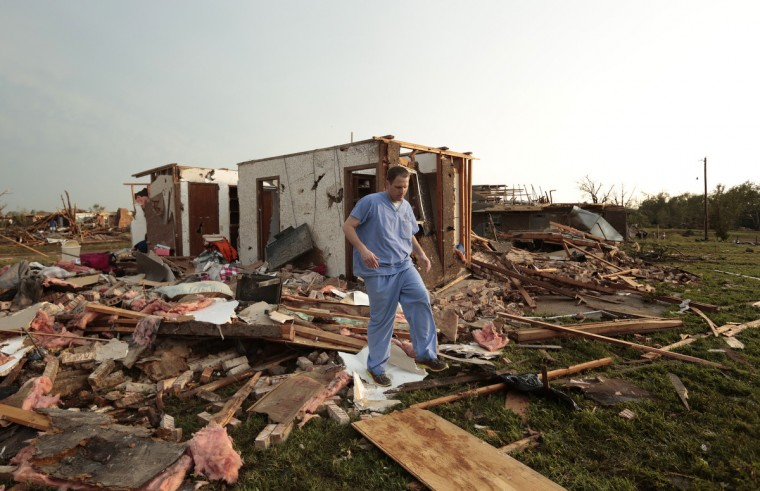 Nathan Ulepich searches outside the back of his house destroyed after a powerful tornado ripped through the area on May 20, 2013 in Moore, Oklahoma. The tornado, reported to be at least EF4 strength and two miles wide, touched down in the Oklahoma City area on Monday killing at least 51 people. (Brett Deering/Getty Images)