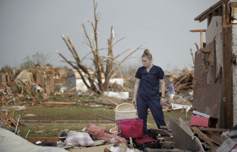 Dana Ulepich looks at the debris from her house destroyed by a powerful tornado ripped through the area on May 20, 2013 in Moore, Oklahoma. The tornado, reported to be at least EF4 strength and two miles wide, touched down in the Oklahoma City area on Monday killing at least 51 people. (Brett Deering/Getty Images)
