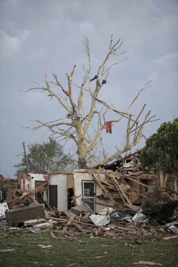 Debris hangs from a tree over a destroyed home after a powerful tornado ripped through the area on May 20, 2013 in Moore, Oklahoma. The tornado, reported to be at least EF4 strength and two miles wide, touched down in the Oklahoma City area on Monday killing at least 51 people. (Brett Deering/Getty Images)
