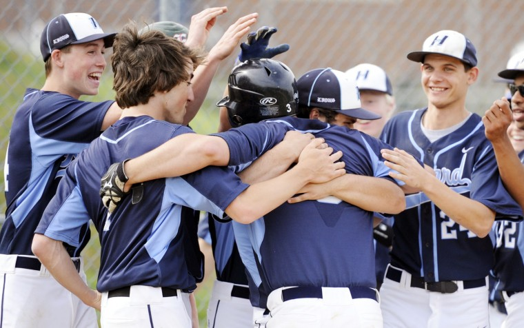 Howard High's Jake Vonella, center, is embraced by his teammates after hitting a home run out of the park in Wednesday's game against Wilde Lake. (Jon Sham/BSMG)