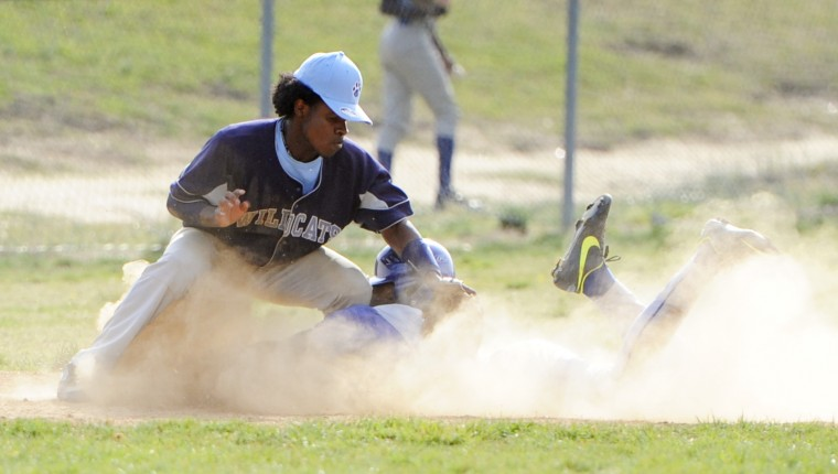 Laurel's Jarvis McClam, right, kicks up some dust as he slides into third base. Northwestern's Bryant Williams makes the tag. (Jon Sham/BSMG)