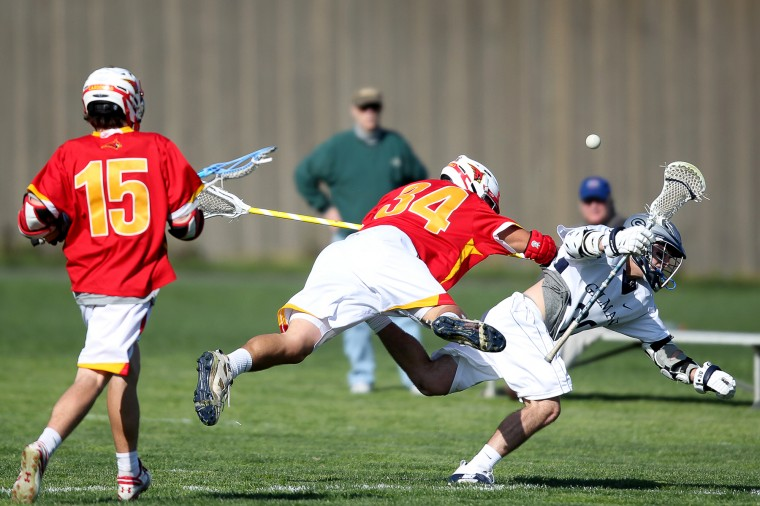 Calvert Hall's Garrett Epple, center, plows through Gilman's Taylor Swindell, right, during the boys lacrosse game at Gilman in Baltimore on Tuesday, April 23, 2013. (Jen Rynda/BSMG)