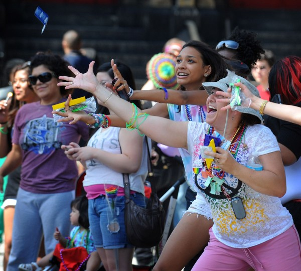 Nancy Quintana (right) of Baltimore and daughter Dominique Stepney, 15, reach for trinkets thrown by Gay and lesbian marchers during the Baltimore Gay Pride parade at Mount Vernon. (Kenneth K. Lam/The Baltimore Sun)