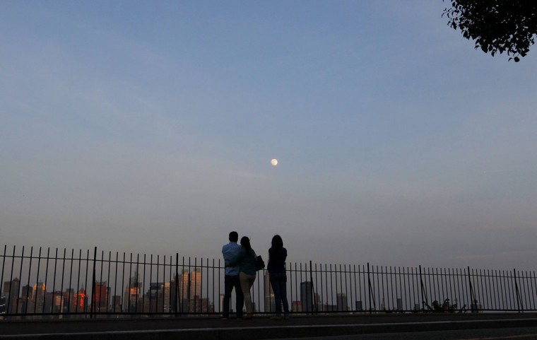 "People watch the moon rise over the skyline of New York from a lookout in Weekhawken, New Jersey, June 21, 2013. On Saturday a perigee moon will coincide with a full moon creating a ""supermoon"" when it will pass by the earth at its closest point in 2013. (Gary Hershorn/Reuters)"