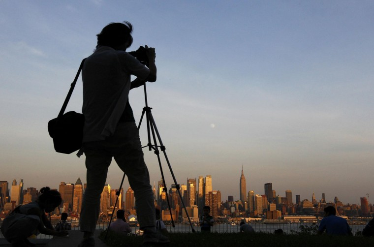 "A woman photographs the moon as it rises over the skyline of New York from a lookout in Weekhawken, New Jersey, June 21, 2013. On Saturday a perigee moon will coincide with a full moon creating a ""supermoon"" when it will pass by the earth at its closest point in 2013. (Gary Hershorn/Reuters)"