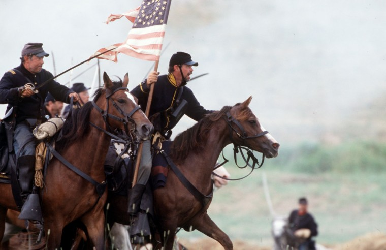 Reenactment of the Battle of Gettysburg: Capt. Craig Beachler and his guidon bearer, Dennis Harlow, lead the Union charge during a reenactment in 2003. (Robert London / Special to The Baltimore Sun)