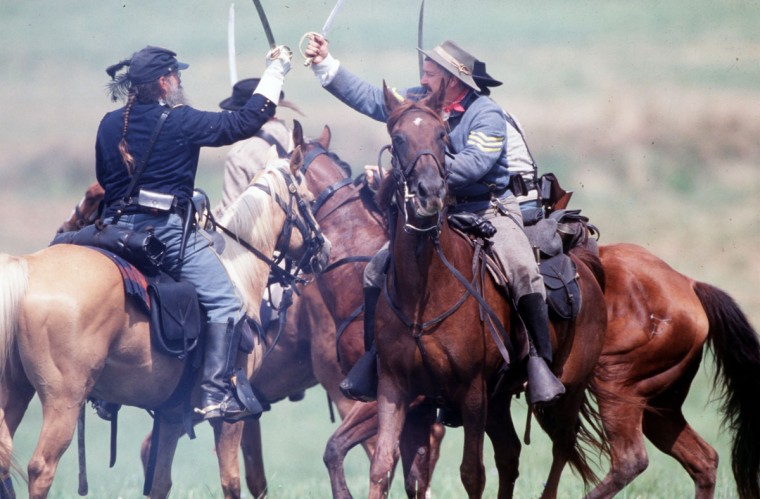 Reenactment of the Battle of Gettysburg: Sgt. Tony Mallory and Capt. Carl Popavick slash at each other during a reenactment in 2003. (Robert London / Special to The Baltimore Sun)