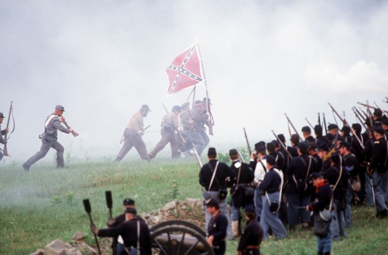 Reenactment of the Battle of Gettysburg: Holding their battle flag high, Confederate troops make a desperate attempt to breech the Union Line during a reenactment in 2003. (Robert London / Special to The Baltimore Sun)