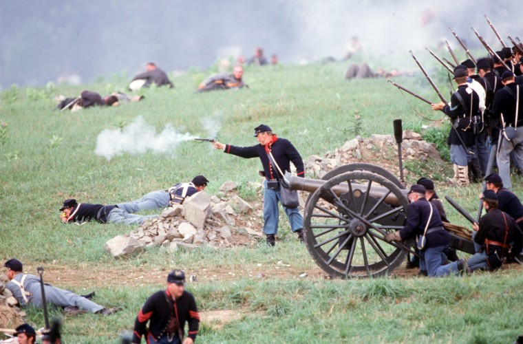 Reenactment of the Battle of Gettysburg: A Union artillery officer fires his pistol at the retreating Confederates during a reenactment in 2003. (Robert London / The Baltimore Sun)