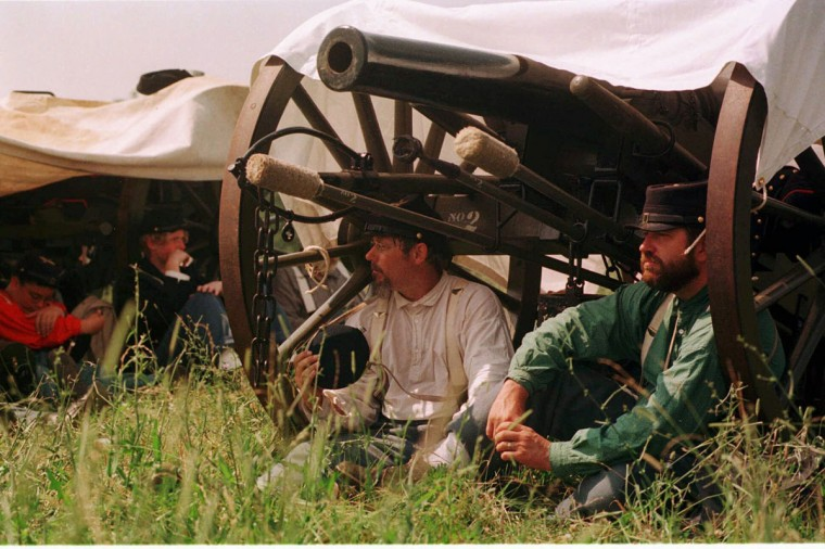 Reenactment of the Battle of Gettysburg: Members of the 3rd Battery, 1st Michigan Light Artillery, Sam Odom (left) of Olivet, Michigan and Erik Linquist of East Lansing, Mich. take cover from the sun during a reenactment in 1998. This is the first Gettysburg reenactment for both. (Jerry Jackson / The Baltimore Sun)