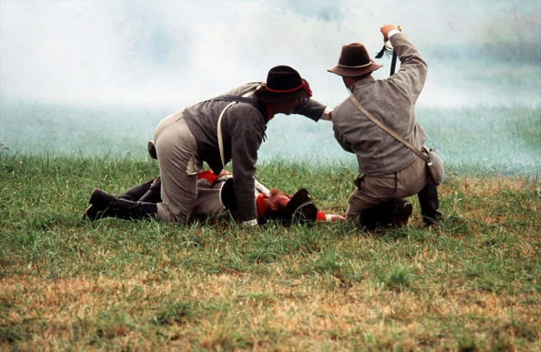 Reenactment of the Battle of Gettysburg: A Union shell finds its mark and a Confederate artilleryman goes down during a reenactment in 2002. (Robert London / Special to The Baltimore Sun)