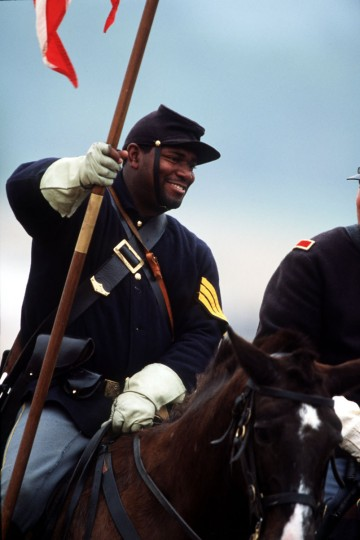 Reenactment of the Battle of Gettysburg: Union color bearer Nat Williams rides into battle during a reenactment in 2002. (Robert London / Special to The Baltimore Sun)