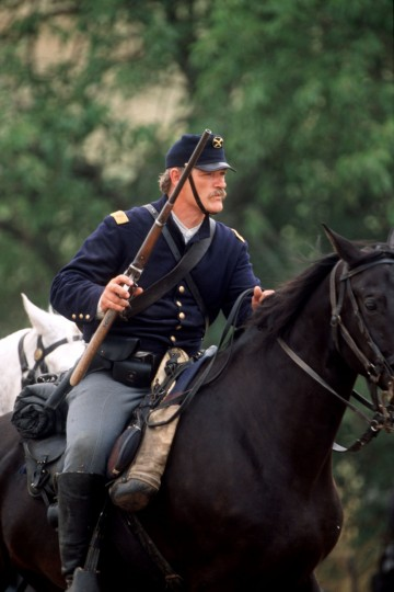 Reenactment of the Battle of Gettysburg: Charlie Doutt of the 2nd U.S. Cavalry moves out with his carbine drawn and ready for action during a reenactment in 2002. (Robert London / Special to The Baltimore Sun)