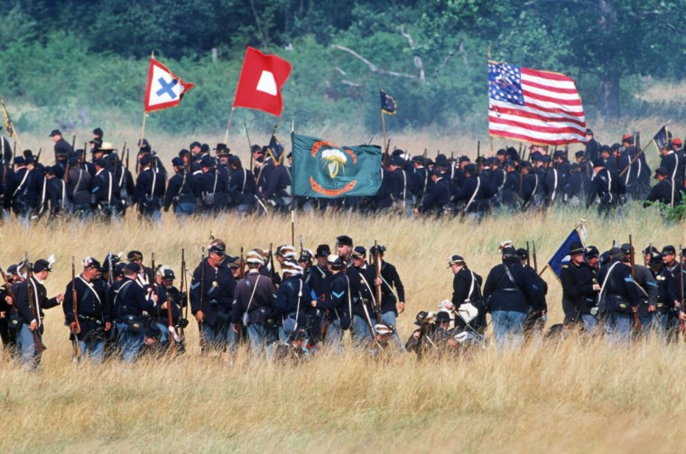 Reenactment of the Battle of Gettysburg: As the Irish Brigade moves forward, exhausted Union troops move to the rear during a reenactment in 2002. (Robert London / Special to The Baltimore Sun)