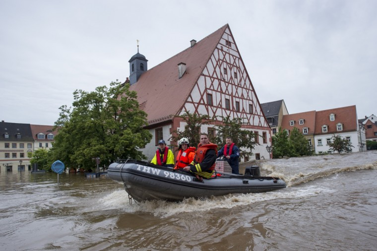 Firefighters and helpers evacuate inhabitants in the flooded city center on June 3, 2013 in Grimma, Germany. Heavy rains are pounding southern and eastern Germany, causing wide-spread flooding and ruining crops. At least two people are missing and feared dead in what is evolving into the most serious flood levels since the so-called 100-year flood of 2002. Portions of Austria and the Czech Republic are also inundated. (Jens Schlueter/Getty Images)
