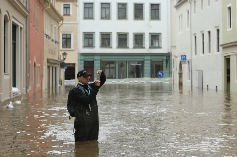 A local resident stands in a street flooded from the nearby Elbe river in the historic city center to take a photograph on June 4, 2013 in Pirna, Germany. Heavy rains have pounded southern and eastern Germany, causing wide-spread flooding and ruining crops. In eastern Germany floodwaters are moving north through the Mulde, Saale and Elbe rivers, forcing authorities to evacuate thousands of residents. (Sean Gallup/Getty Images)