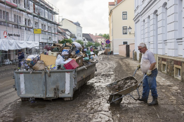 Inhabitants and others work in the city center of Grimma after the flood waters have subsided on June 4, 2013 Grimma, Germany. Heavy rains have pounded southern and eastern Germany, causing wide-spread flooding and ruining crops. In eastern Germany floodwaters are moving north through the Mulde, Saale and Elbe rivers, forcing authorities to evacuate thousands of residents. (PJens Schlueter/Getty Images)