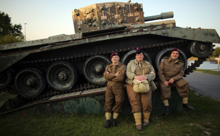 People dressed in Second World War uniforms sit on a tank close to the Pegasus Bridge Memorial Museum near Caen, France. (Matt Cardy/Getty Images)