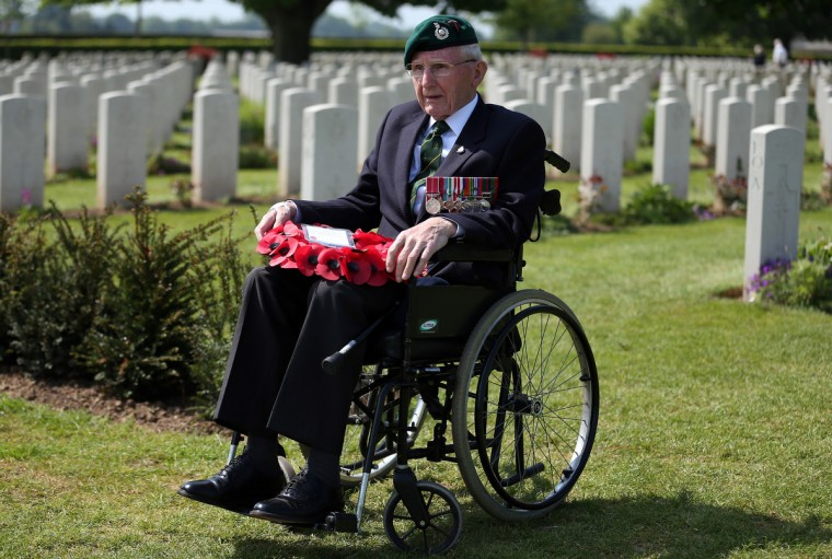 Normandy Veteran 90-year-old Jim Kelly, (a Royal Marine who landed on Sword Beach on D-Day) carries a wreath at a remembrance and wreath laying ceremony to commemorate the start of the D-Day landings at Bayeux War Cemetery. (Matt Cardy/Getty Images)