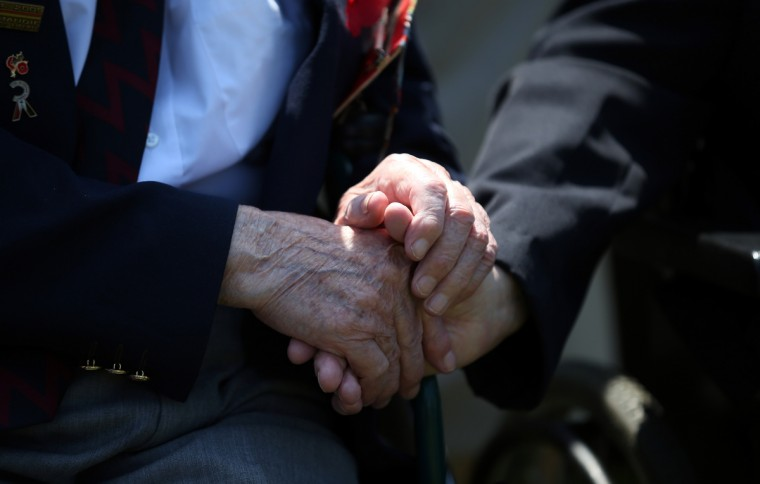 Two Normandy Veterans clasp hands at a remembrance and wreath laying ceremony to commemorate the start of the D-Day landings at Bayeux War Cemetery. (Matt Cardy/Getty Images)
