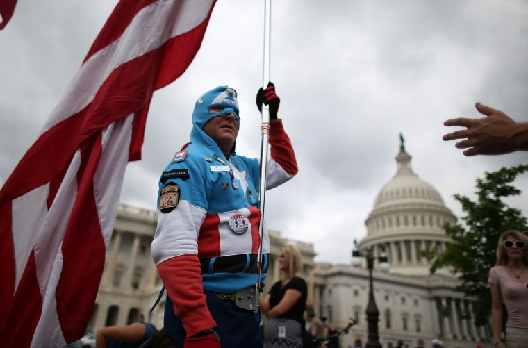 Jim Griffin (L), dressed as Capt. America, holds a large American flag while participating in a Tea Party rally at the U.S. Capitol in Washington, DC. The group Tea Party Patriots hosted the rally to protest against the Internal Revenue Service's targeting Tea Party and grassroots organizations for harassment. (Mark Wilson/Getty Images)