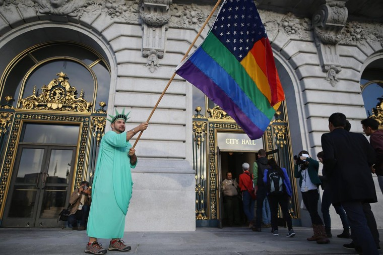 A gay rights supporter waves a flag at City Hall June 26, 2013 in San Francisco, United States. (Justin Sullivan/Getty Images)