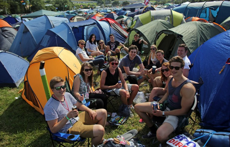 A group of friends sit with the recently erected tents at the Glastonbury Festival of Contemporary Performing Arts site at Worthy Farm, Pilton on June 26, 2013 near Glastonbury, England. (Matt Cardy/Getty Images)