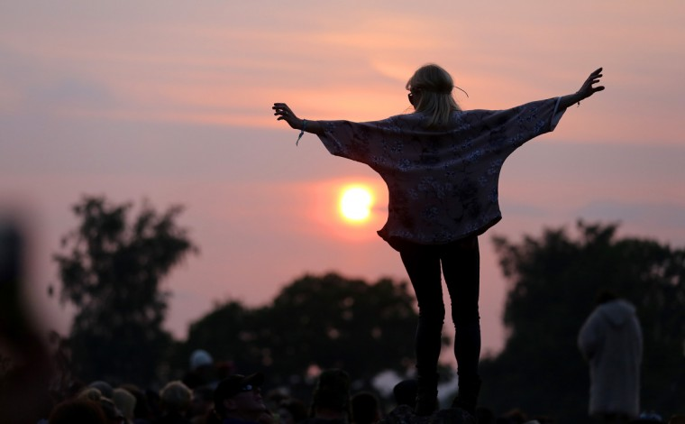 A woman stands on a rock at the stone circle as people gather for sunset at the Glastonbury Festival of Contemporary Performing Arts site at Worthy Farm, Pilton on June 26, 2013 near Glastonbury, England. (Matt Cardy/Getty Images)