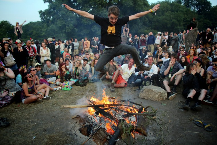A man jumps over a fire that has been lit inside the stone circle as people gather for sunset at the Glastonbury Festival of Contemporary Performing Arts site at Worthy Farm, Pilton on June 26, 2013 near Glastonbury, England. (Matt Cardy/Getty Images)