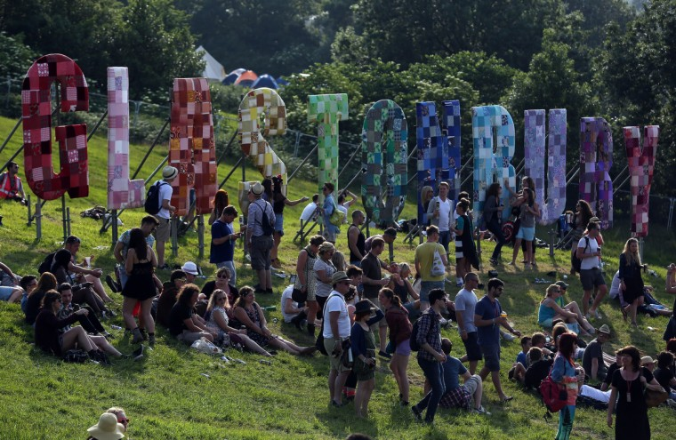 People sit in the sun below the Glastonbury sign at the Glastonbury Festival of Contemporary Performing Arts site at Worthy Farm, Pilton on June 26, 2013 near Glastonbury, England. (Matt Cardy/Getty Images)
