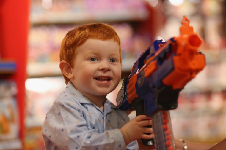 Tristan, aged 2, holds a 'Nerf Rapidstrike CS-18' toy gun in Hamleys toy shop in London, England. The gun, which retails for 50 GBP and has a range of 75 feet, is included in Hamleys' predictions for the top selling toys for Christmas 2013. (Oli Scarff/Getty Images)